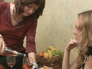 Two girls swallow wine and talk