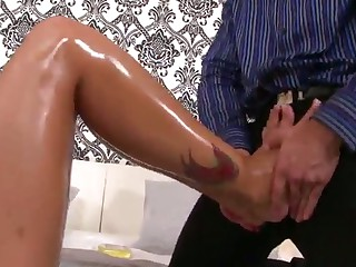 Laura Lee with tattooed long legs giving footjob