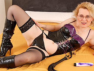 Blond granny in a dominatrix outfit masturbates in her couch