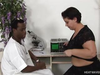 dark doctor examines woman's big boobs
