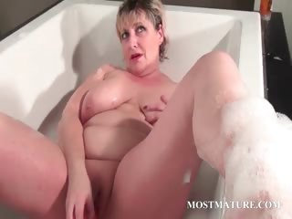 Aged tramp dildoes pussy in bathtub